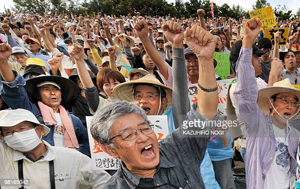 People raise their hands as they stage a rally against the US military base in Ginowan Okinawa Prefecture on November 8 2009 Thousands rallied...