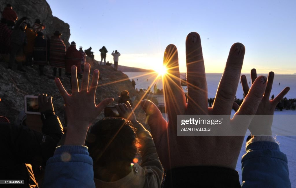 People raise their hands during a ritual at sunrise to celebrate the Aymara New Year on June 21, 2013 at the Uyuni salt flat in Bolivia. A crowd gathered to receive the first rays of Tata Inti (god Sun) during the celebration of the winter solstice that marks the beginning of the 5521st year in the Aymara calendar. AFP/PHOTO/Aizar RALDES