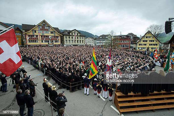 People raise their hands to vote during the annual Landsgemeinde meeting at a square in the town of Appenzell eastern Switzerland on April 28 2013...