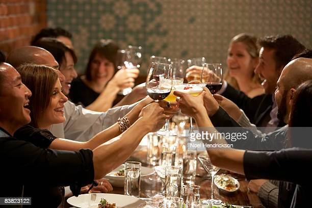 people raising glasses at restaurant
