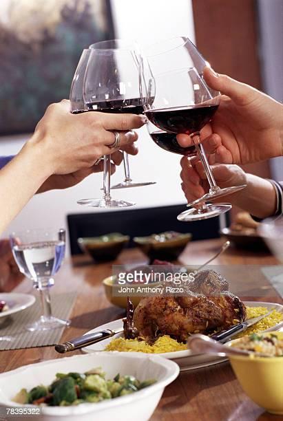 People raising glasses in red wine toast