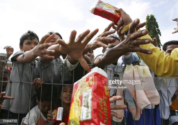 People reach for aid at an airport January 1 2005 in Banda Aceh Aceh Province Sumatra Indonesia Much of the Islands western coast was destroyed in...