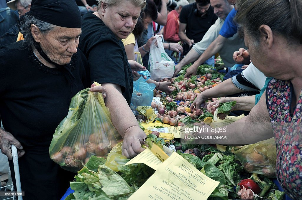 "People reach for free fruit and vegetables distributed by farmers' market vendors as part of their protest marking their 24-hour strike on May 15, 2013. Vendors at Greece's open-air street markets, known as ""laiki,"" are on strike protesting the government's plans to facilitate entry into the profession. AFP PHOTO/ LOUISA GOULIAMAKI"