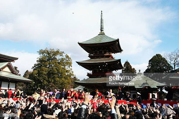 People reach out for the beans thrown by sumo wrestlers at the Shinshoji Temple to celebrate the coming of spring based on the lunar calender on...