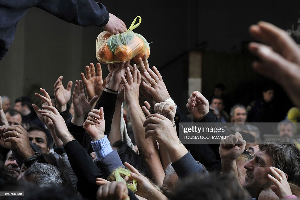 People reach out reach out for a bag of oranges during a free distribution of fruit and vegetables by Greek farmers outside the Agriculture Ministry in Athens part a farmers protest against high production costs, including petrol, on February 6, 2013. Farmers distributed more than 50 tons of fruit and vegetables.