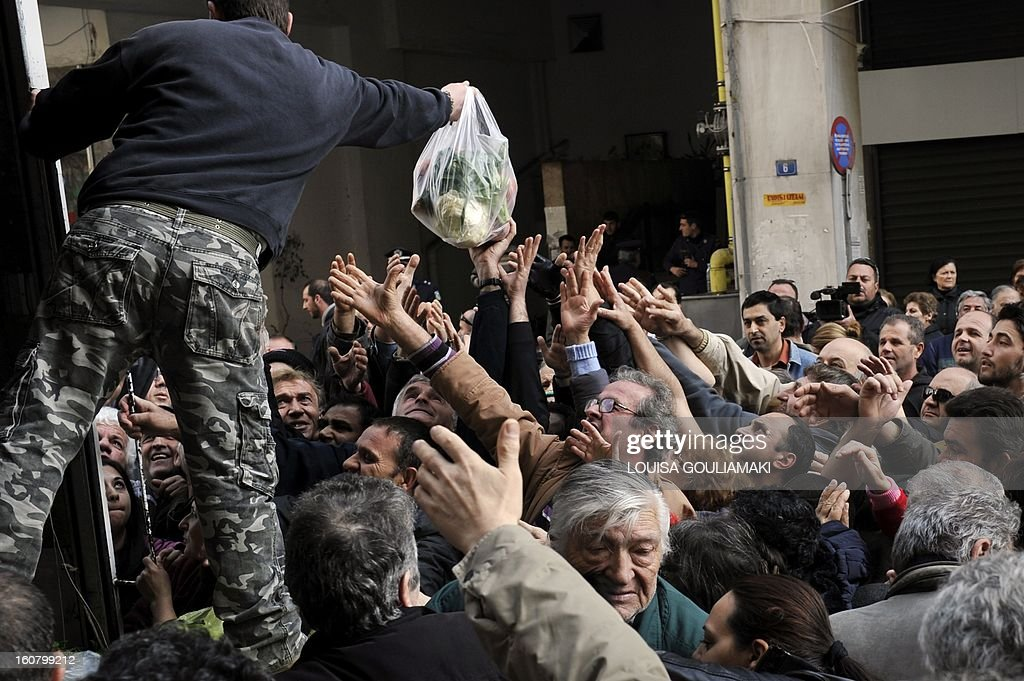 People reach out reach out for a bag of vegetables during a free distribution of fruit and vegetables by Greek farmers outside the Agriculture Ministry in Athens part a farmers protest against high production costs, including petrol, on February 6, 2013. Farmers distributed more than 50 tons of fruit and vegetables.