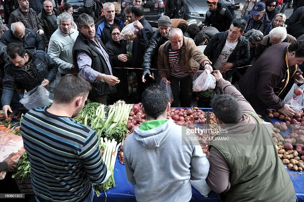 People reach out reach out for a bags of fruit and vegetables during a free distribution by Greek farmers outside the Agriculture Ministry in Athens part a farmers protest against high production costs, including petrol, on February 6, 2013. Farmers distributed more than 50 tons of fruit and vegetables.
