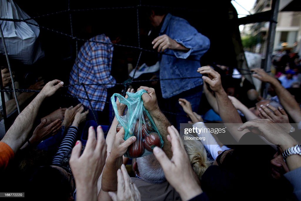People reach out to receive free bags of leftover vegetables handed out by striking street vendors in Athens, Greece, on Wednesday, May 15, 2013. Greece's plans to return to international bond markets next year reflect the government's confidence it can draw a line under the country's debt crisis although the cost of borrowing suggests that might be premature. Photographer: Kostas Tsironis/Bloomberg via Getty Images
