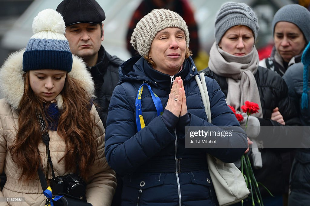 People react after laying flowers for anti-government demonstrators killed in clashes with police in independence square on February 23, 2014 in Kiev, Ukraine. Prime Minister Yanukovych is said to have left Kiev for a eastern stronghold as the country's parliament voted to remove Yanukovych from office and call for new elections.
