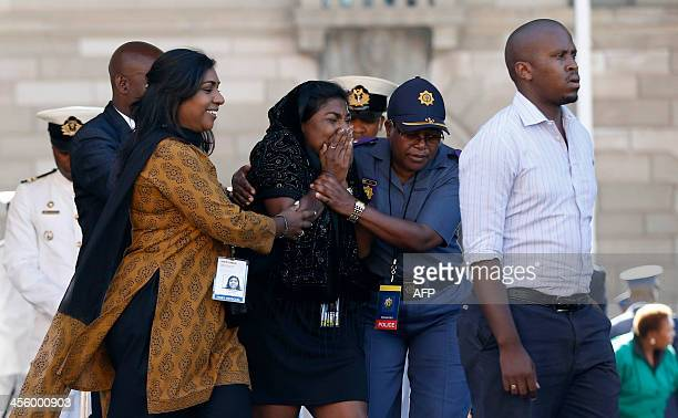People react after walking past the casket containing South African former president Nelson Mandela on the last day of Mandela's lying in state at...
