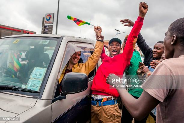 TOPSHOT People react and wave Zimbabwean national flags during a demonstration demanding the resignation of Zimbabwe's president on November 18 2017...