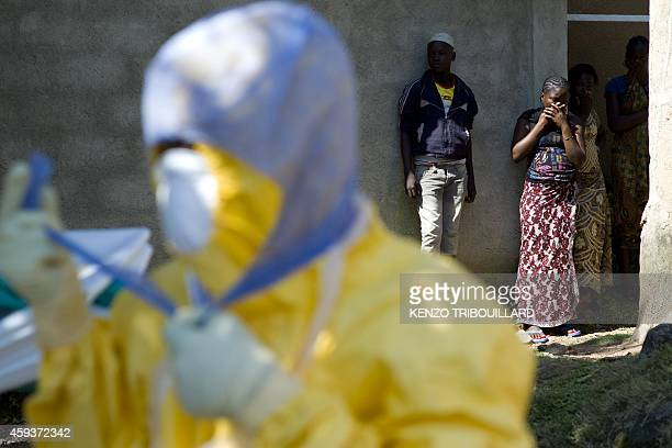 People react as Guinean Red Cross workers arrive to remove the corpse of a neighbour who died of Ebola in Macenta on November 21 2014 The World...