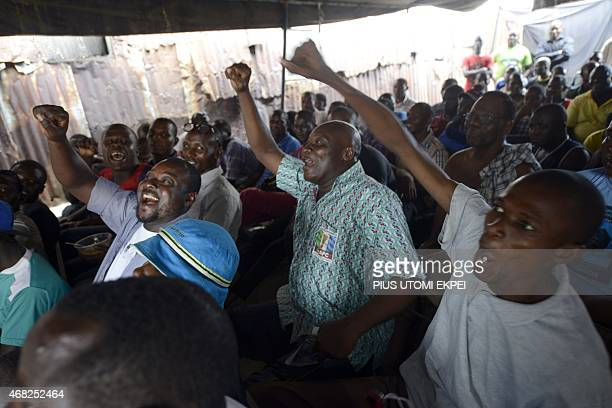 People react as partial results of the Nigerian presidential elections are released by the Independent National Electoral Commission indicating the...