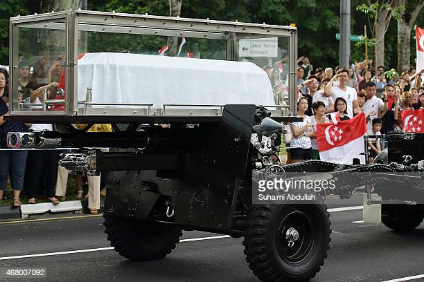 People react as the cortege of the late Mr Lee Kuan Yew passes by Upper Thomson Road on its way for a private cremation service at Mandai Crematorium...