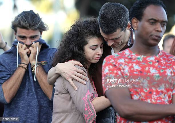 People react as they gather at a makeshift memorial to pay tribute to the victims of an attack in the French Riviera city of Nice on July 15 a day...
