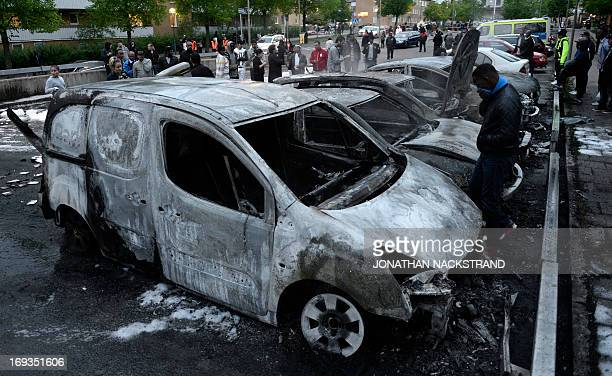 People react as they inspect the scene of cars gutted by fire in the Stockholm suburb of Rinkeby after youths rioted in several different suburbs...