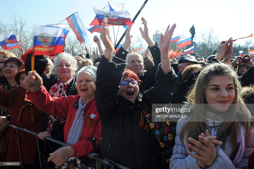 People react as they listen to a speech of Russian president broadcast on a giant screen in Sevastopol, on March 18, 2014. President Vladimir Putin has backed the approval of a draft agreement which would incorporate Ukraine's region of Crimea into Russian territory, according to an official instruction published today.