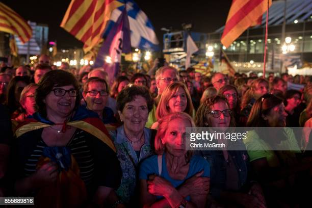 People react as they listen to Catalan President and proindependence leader Carles Puigdemont speak at the closing meeting of the final...