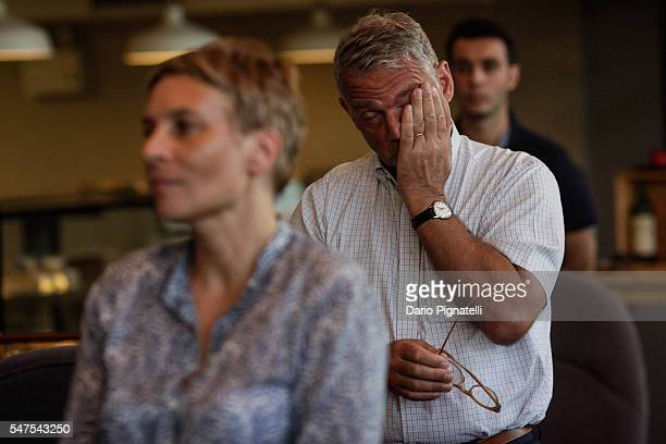 People react as they observe a minute of silence during a vigil for the victims of the attack in the French city of Nice at the Alliance Francaise on...