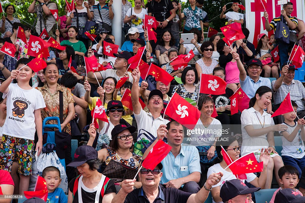 People react as they raise Chinese and Hong Kong flags during the open day of the Chinese People's Liberation Army (PLA) Navy Base at Stonecutter Island in Hong Kong on July 1, 2016, to mark the 19th anniversary of the Hong Kong handover to China. / AFP / Anthony Wallace