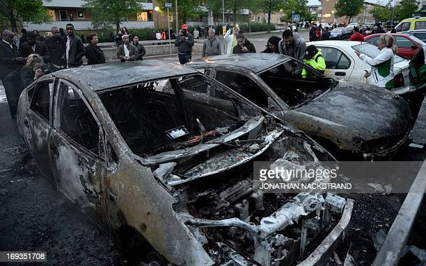 People react as they stand around cars gutted by fire in the Stockholm suburb of Rinkeby after youths rioted in several different suburbs around...