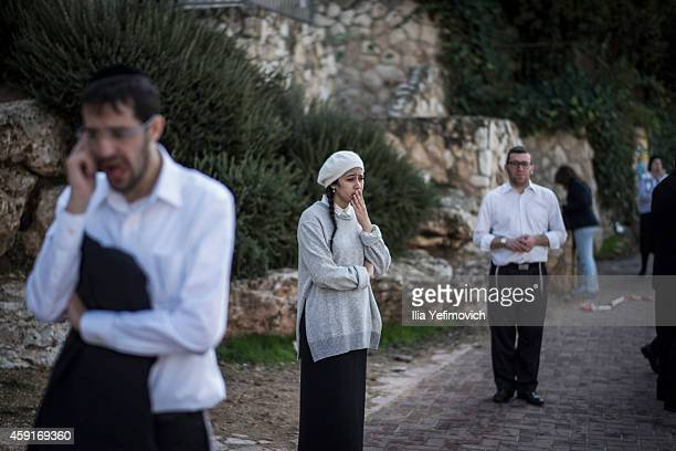 People react as they stand outside a synagogue on November 18 2014 in Jerusalem Israel Four Israelis have been killed and several others wounded in a...