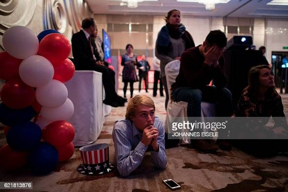 TOPSHOT People react as they watch news on a screen to follow the results of the final day of the US presidential election at an event organised by...