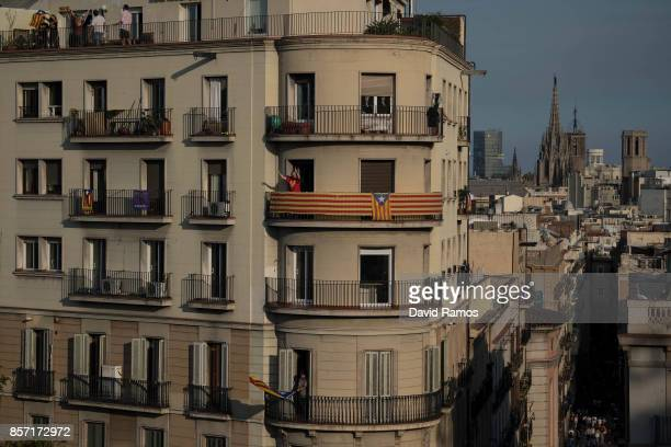 People react from their balconies as they protest during a regional general strike to protest against the violence that marred Sunday's referendum...