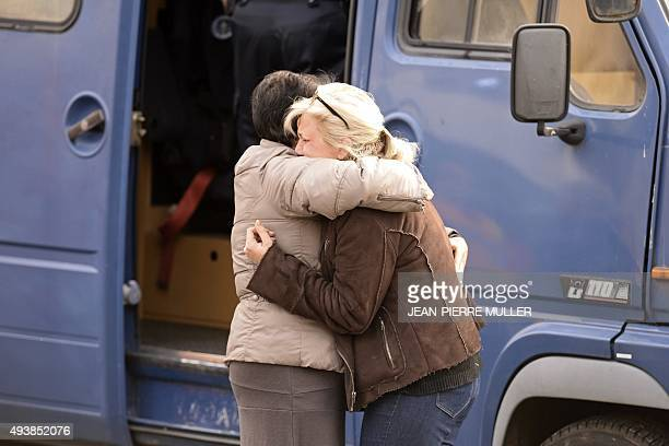 People react on October 23 2015 in Puisseguin near Libourne southwestern France following a road accident in which at least 42 people most of them...