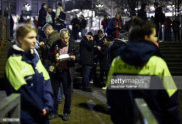 People react shortly after the match between Germany and the Netherlands was cancelled following a bomb alert at the HDIArena on November 17 2015 in...