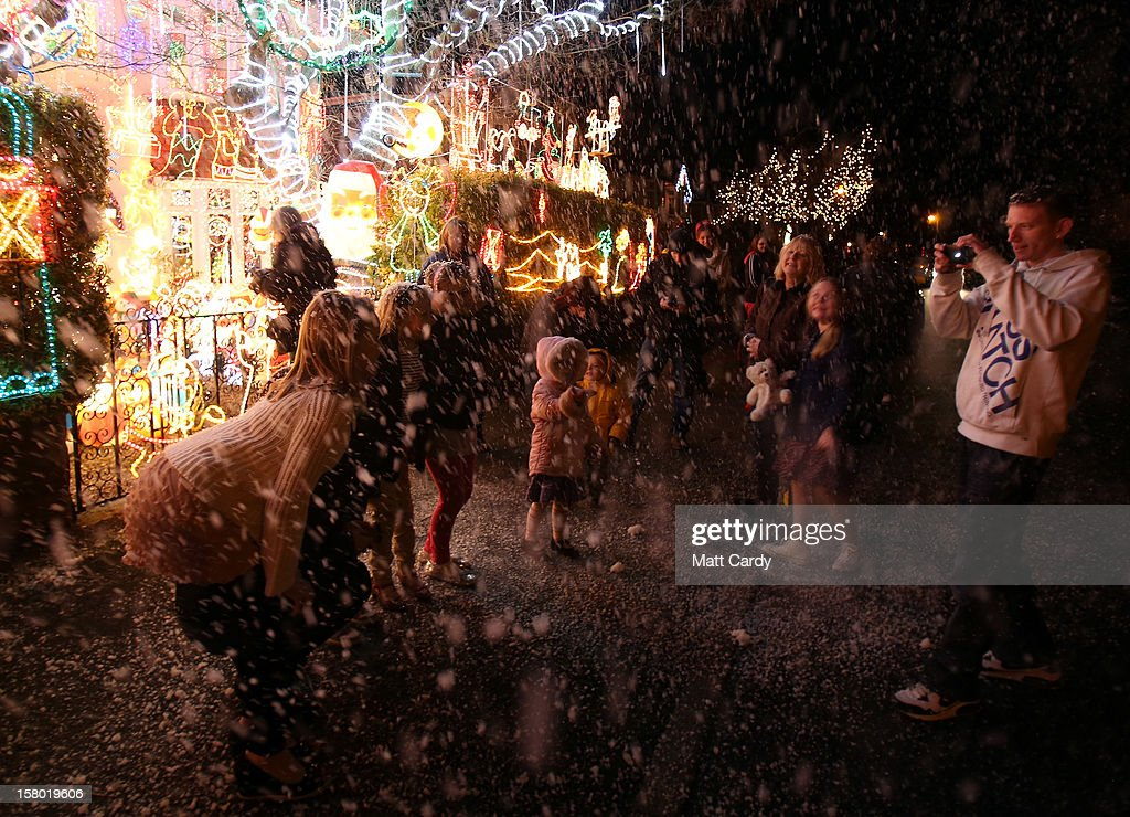 People react to a snow machine as they gather to look at Christmas festive lights that adorn a detached house in a suburban street in Melksham, December 8, 2012 in Melksham, England. The lights, a popular festive attraction, have returned to the town after a two-year absence and have raised thousands of pounds for charity for a local hospice, Dorothy House. The display, which is estimated to involve over 100,000 bulbs, worth over 30,000 GBP and even needed an up-rated electricity supply installed to cope with the additional power needed, is the brainchild of householder and electrician Alex Goodhind. This year, the display which Mr Goodhind began fifteen years ago now takes a team of professional electricians five weeks to complete, and even includes a snow machine.
