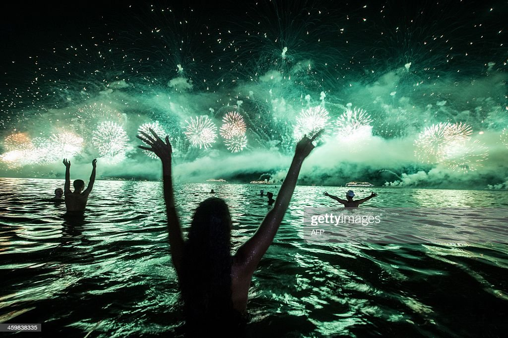 People react to the fireworks on the new year's celebration at Copacabana beach in Rio de Janeiro Brazil on January 1 2014 AFP PHOTO / YASUYOSHI...