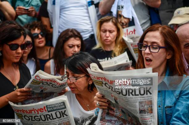 People read a copy of today's Cumhuriyet daily newspaper on July 28 2017 during a demonstration in front of Istanbul's courthouse A Turkish court was...