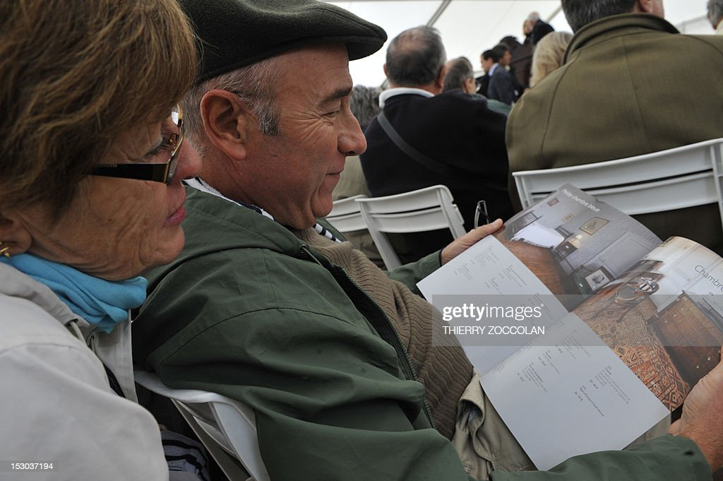 People read an auction brochure as they attend the auction of the furniture of the Chateau de Varvasse (Varvasse castle) belonging to France's former president Valery Giscard d'Estaing, on September 29, 2012 in Chanonat, central France.