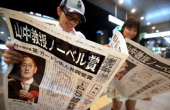 People read an extra edition of newspaper distributed to celebrate Kyoto University professor Shinya Yamanaka winning the Nobel prize at Fukuoka...