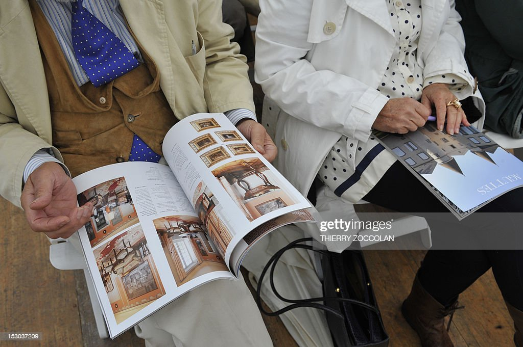People read auction brochures as they attend the auction of the furniture of the Chateau de Varvasse (Varvasse castle) belonging to France's former president Valery Giscard d'Estaing, on September 29, 2012 in Chanonat, central France. AFP PHOTO THIERRY ZOCCOLAN
