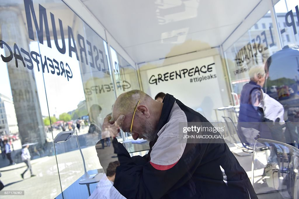 People read classified papers from the ongoing US-EU trade talks, presented to the public by Greenpeace in a glas container near the Brandenburger Gate, in Berlin on May 2, 2016. Greenpeace published documents showing that the Transatlantic Trade and Investment Partnership (TTIP) poses 'major risks for climate, environment and consumer safety'. / AFP / John MACDOUGALL