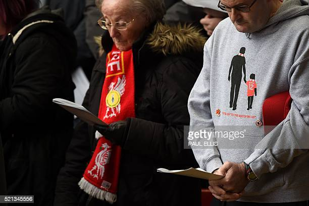 People read from the order of service during a memorial service at Anfield in Liverpool north west England on April 15 on the 27th anniversary of the...