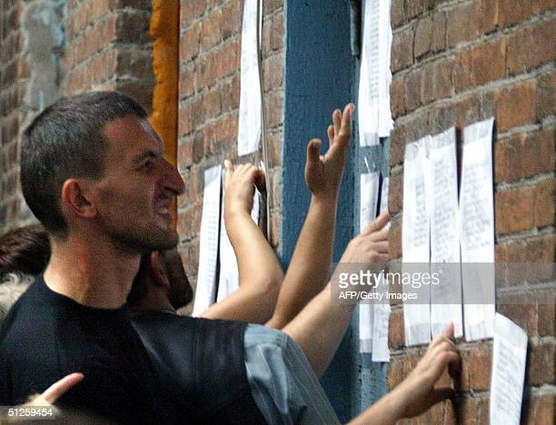 People read lists of hospitalized hostages on the wall of Beslan's local hospital northern Ossetia 03 September 2004 More than 100 people were...