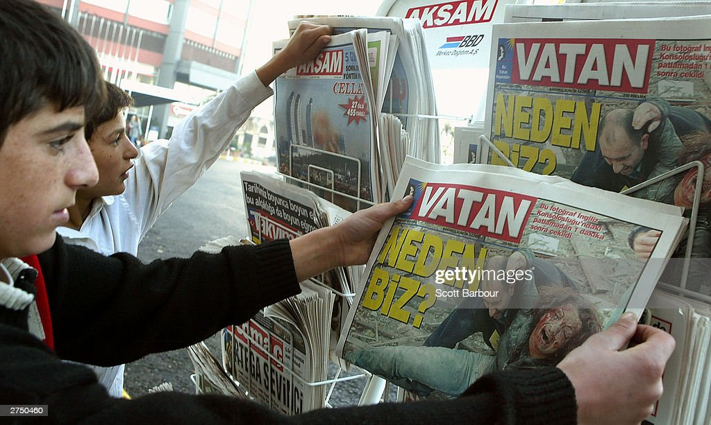 People read the front pages of local newspapers near the scene of the British Consulate bombing November 21, 2003 in Istanbul, Turkey. Bomb attacks on the British consulate and the HSBC bank headquarters on November 20, 2003 killed at least 27 people and left hundreds injured.