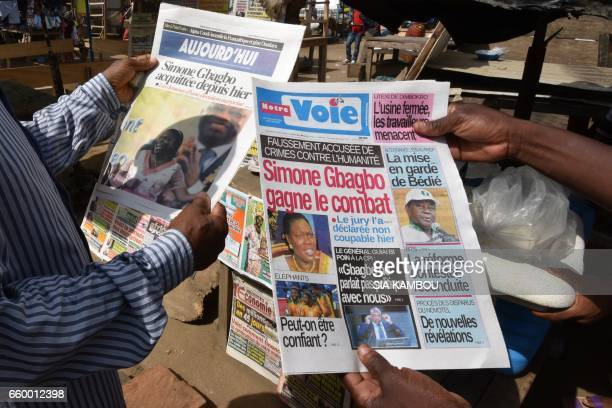 People reads newspapers reporting the acquittal of former first lady Simone Gbagbo on March 29 2017 in Abidjan one day after an Ivory Coast jury...