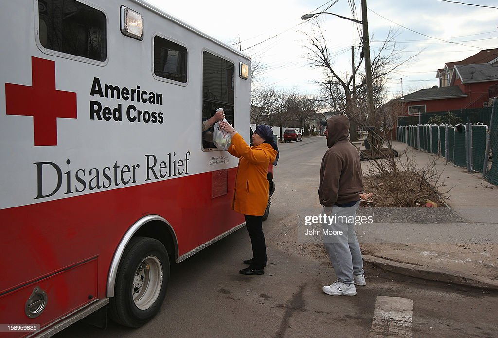 People receive aid from a Red Cross mobile distribution center on January 4, 2013 in the Midland Beach area of the Staten Island borough of New York City. More than two months after the storm, Congress passed legislation today that will provide $9.7 billion to cover insurance claims filed by people whose homes were damaged or destroyed by Sandy.