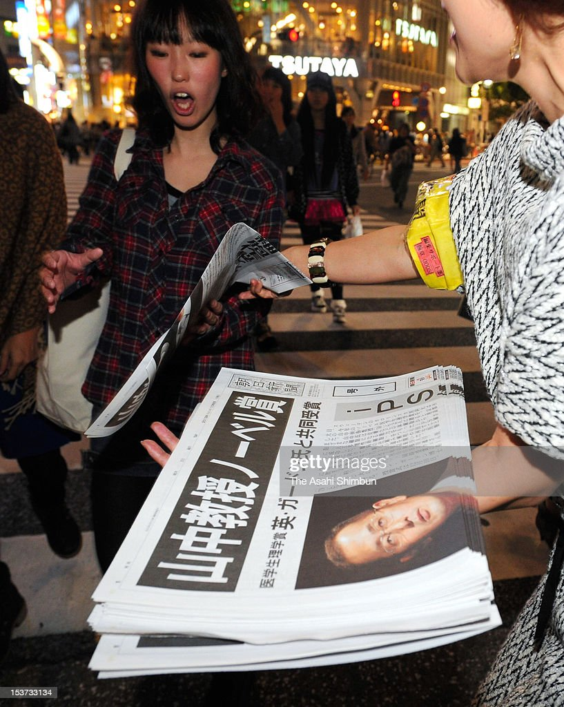 People receive extra edition of newspapers distributed to celebrate Kyoto University professor Shinya Yamanaka winning the Nobel prize on October 8, 2012 in Tokyo, Japan. Yamanaka and Sir John Gurdon have both been awarded the Nobel prize for medicine or physiology for their work as pioneers of stem cell research.