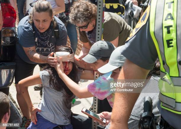 People receive firstaid after a car accident ran into a crowd of protesters in Charlottesville VA on August 12 2017 A picturesque Virginia city...