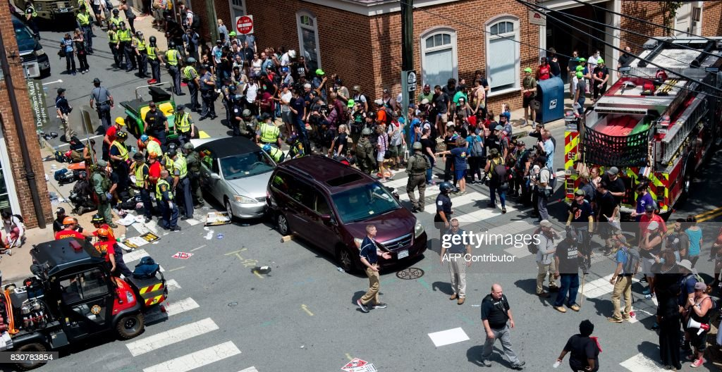 People receive first-aid after a car accident ran into a crowd of protesters in Charlottesville, VA on August 12, 2017. A vehicle plowed into a crowd of people Saturday at a Virginia rally where violence erupted between white nationalist demonstrators and counter-protesters, witnesses said, causing an unclear number of injuries. /