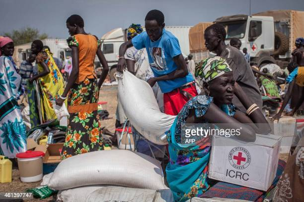 People receive food aid and other items such as soap plastic mats and buckets from a recent ICRC delivery in Minkammen 25 kilometres south of Bor on...