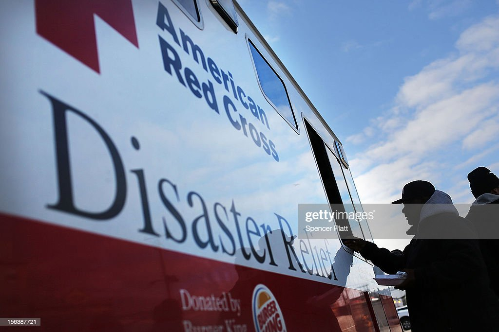 People receive free food from the American Red Cross in the heavily damaged Rockaway neighborhood where a large section of the iconic boardwalk was washed away on November 14, 2012 in the Queens borough of New York City. Two weeks after Superstorm Sandy slammed into parts of New York and New Jersey, thousands are still without power and heat.