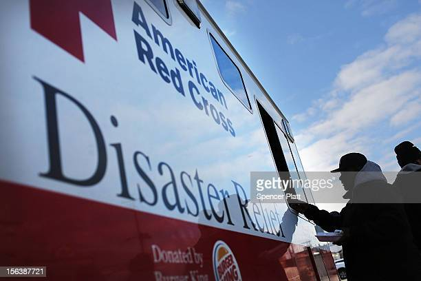 People receive free food from the American Red Cross in the heavily damaged Rockaway neighborhood where a large section of the iconic boardwalk was...