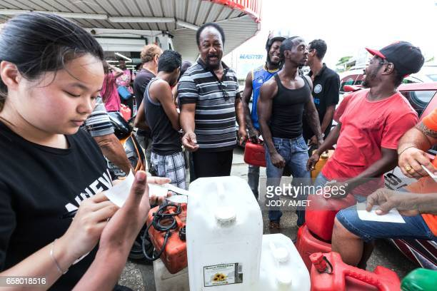 People receive numbered coupons at an outoffuel petrol station in order to organise distribution of a future resupply on March 26 in Cayenne French...