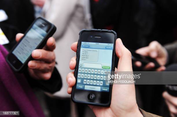 People receive sms on their mobile phone on April 22 2012 in front of the Socialist Party headquarters in Paris following the announcement of the...